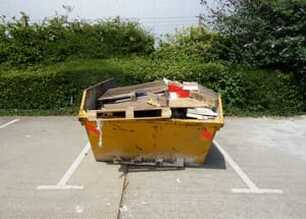 Commercial skip in carpark bay filled with pallets