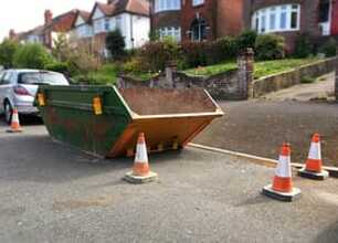 Large skip on road with coned off area around it