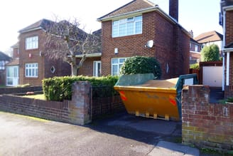Large skip in narrow driveway filled with domestic waste